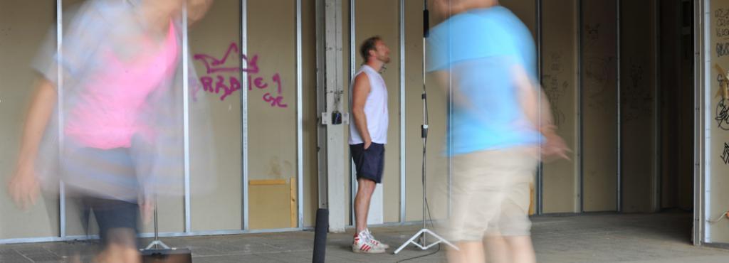 Eine Bananenkiste, in die ein Mikrofon installiert wurde. Um die Kiste herum laufen zwei Männer. Durch verzerrte Unschärfe sind sie nicht zu erkennen. Im Hintergund: Eine weitere Person vor einem Mikrofon.