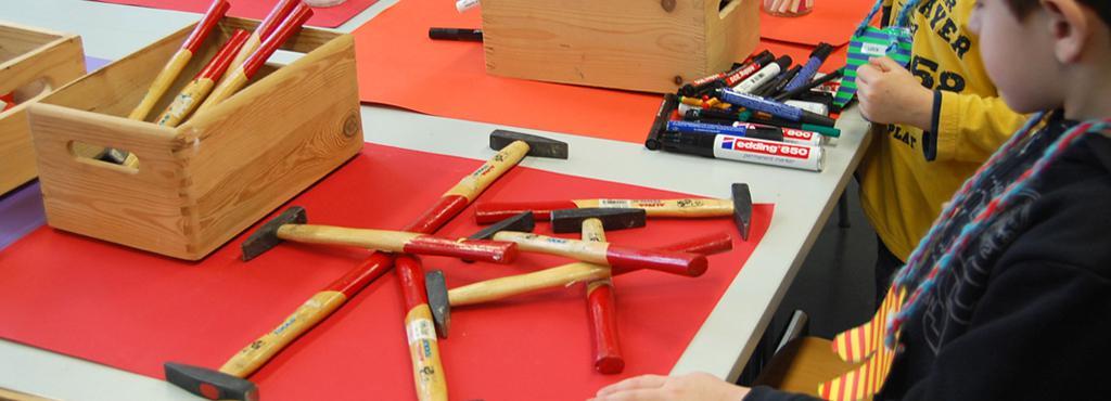 Kinder können sich in kleinen Handwerksarbeiten erproben. Dazu bekommen sie Hämmer und Stifte gestellt.
