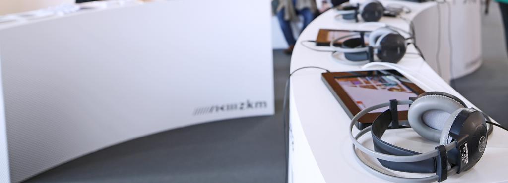 Ein geschwungener Tresen, auf dem iPads und Kopfhörer liegen