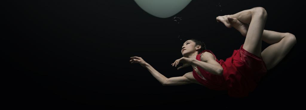 Ein überdimensionales weißes Herz, unter dem eine Frau schwimmt
