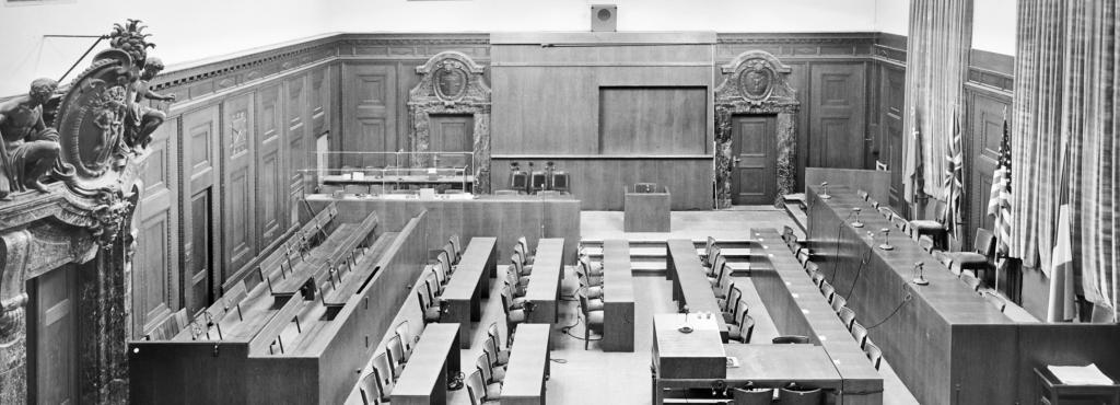 Schwarz-weiße Fotografie aus dem Jahr 1945, die den leeren Raum 600 des Nürnberger Justizpalastes zeigt.