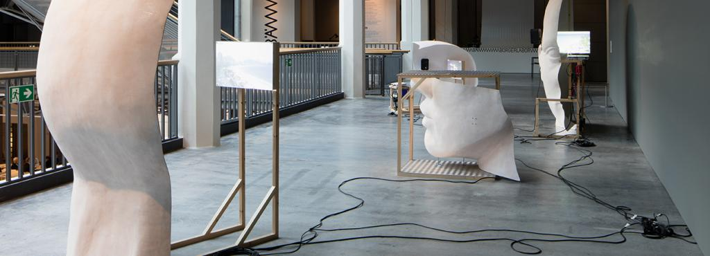 Work composed of big white heads with wood structures and screens