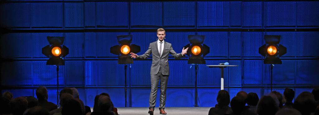 Ein Mann im Anzug steht auf einer Bühne.