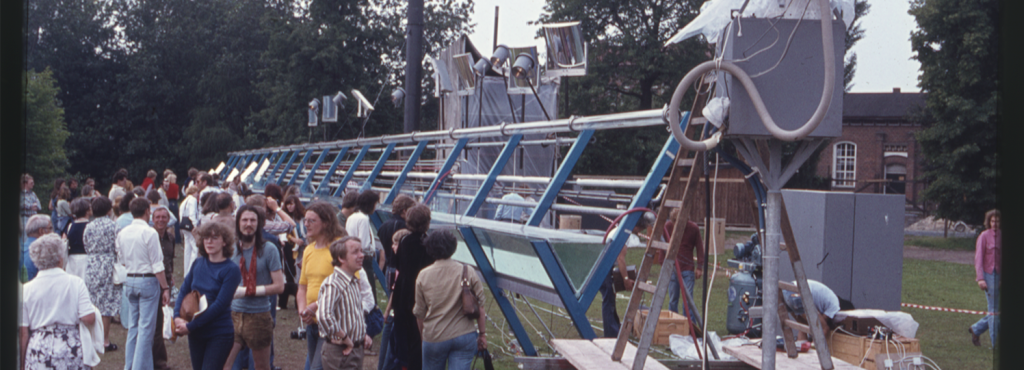 Eine Menschenmenge steht neben einer großen Installation im Freien, man sieht Bäume im Hintergrund