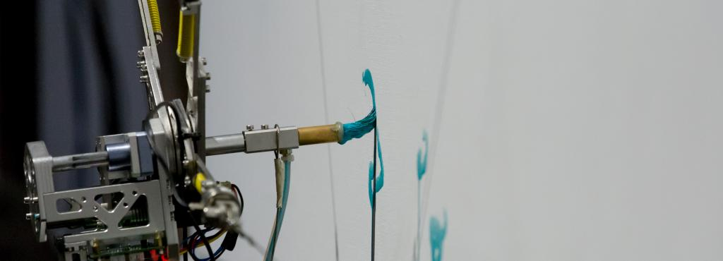 The picture shows a robot-controlled brush, drawing turquoise color on a white canvas.