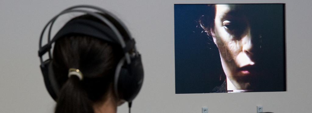 Eine Frau mit Kopfhörer betrachtet ein Video einer anderen Frau.