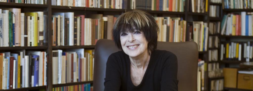 Eine Frau sitzt in einem Sessel vor einem großen Bücherregal.