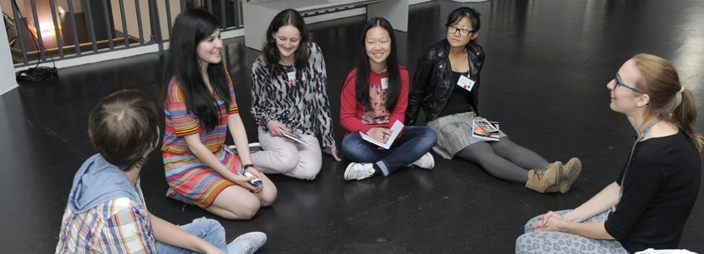 Mehrere Mädchen und ein Junge sitzen im Halbkreis und haben Schreibutensilien vor sich auf dem Schoß oder auf dem Boden liegen.