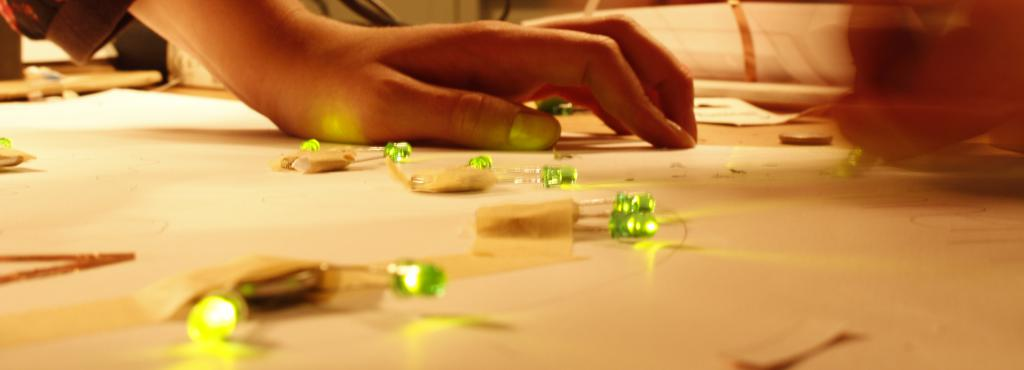 One can see a hand, that is leaning on a table on which - taped to a sheet of paper - green LEDs are glowing.