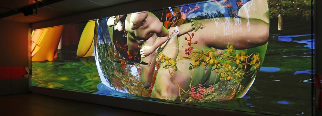Eine Projektion auf Leinwand zeigt bunte, surreale Computeranimationen