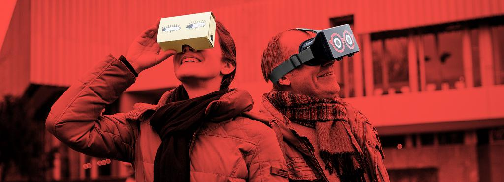 The photo shows a man and a woman, both wearing a HoloLens glasses. Above the photo is a red filter.