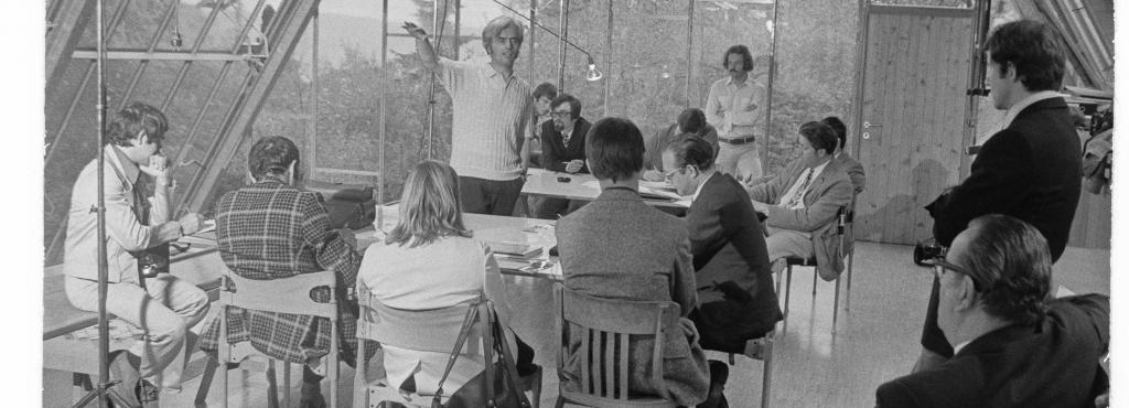 An old black-and-white shot of architect Frei Otto, standing in a circle of listeners