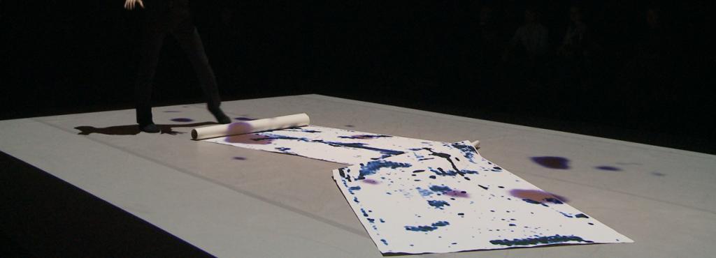 Das Bild zeigt einen Tänzer, der auf einer bemalten Plakatrolle steht.