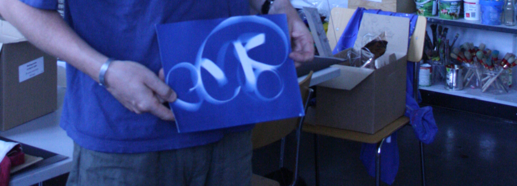 A man is holding a photogram on which the form of a curly object is showing.