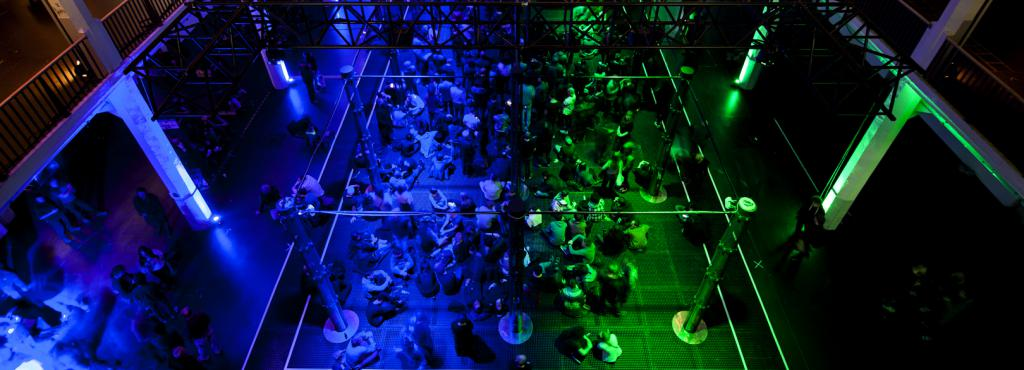 The picture shows the fully filled green and blue illuminated ZKM foyer