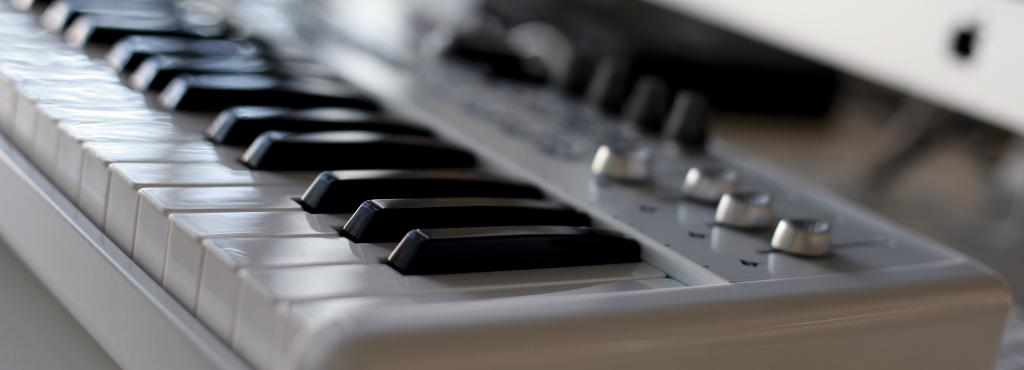 A keyboard in a close shot, that is attached to a computer in the background.