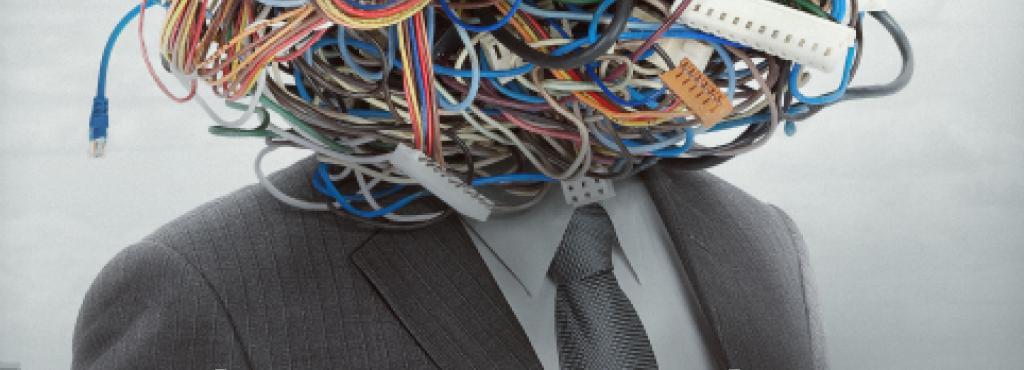 Ein Oberkörper im Anzug, als dessen Kopf Ein kreisförmiger Kabelsalat dient.