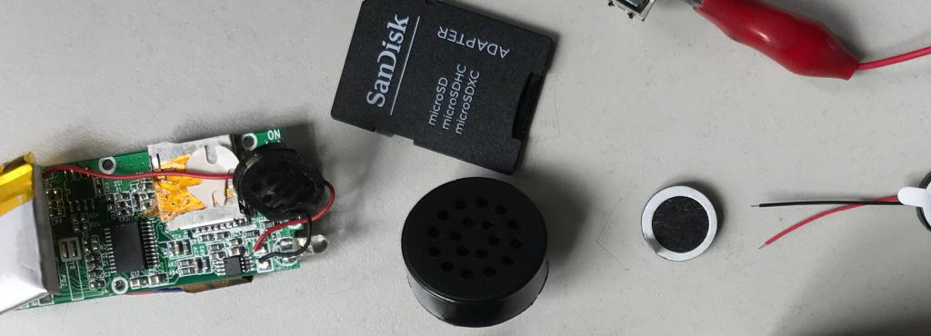 Technische Geräte und eine SD-Karte auf einer grauen Tischplatte