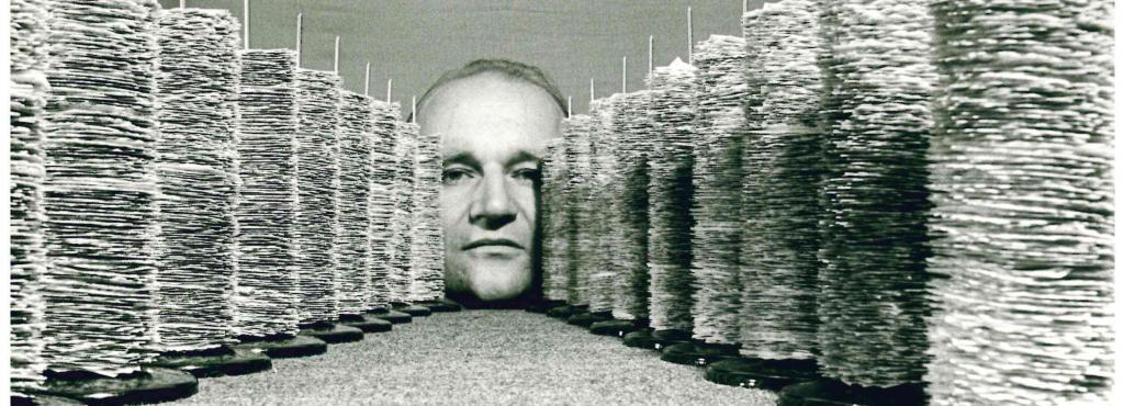 Das Schwarz-Weiß-Bild zeigt eine Fotocollage, auf der mittig das Gesicht eines älteren Mannes zu sehen ist, das links und rechts von mehreren aneinandergereihten, auf ihn zugehenden diagonalen Zettelspießen umrandet wird.