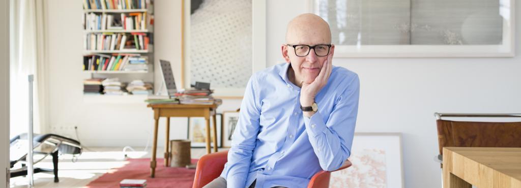 Professor Bude sitzt auf einem roten Stuhl in einer Wohnung mit Bücherregal und Schreibtisch, den Kopf auf die Hand gestützt.