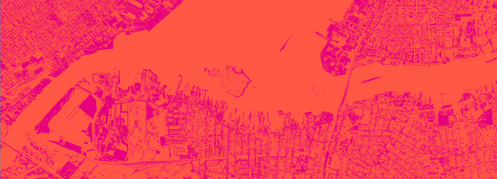 From the bird's eye view you can see a city with river and many houses. The picture is in red and purple.