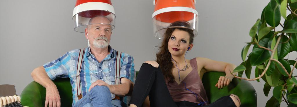 Zwei Personen sitzen auf einem grünen Sofa, ihre Köpfe stecken unter einer Friseurhaube.´