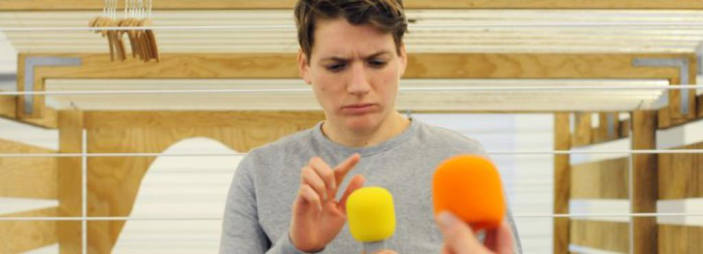 Ein junger Mann tippt kritisch mit seinem Finger auf ein gelbes Mikrofon. Er ist von verschiedenen Mikrofonen umgeben.