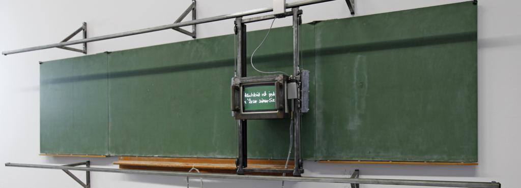 Ein Monitor auf Schienen vor einer grünen Tafel