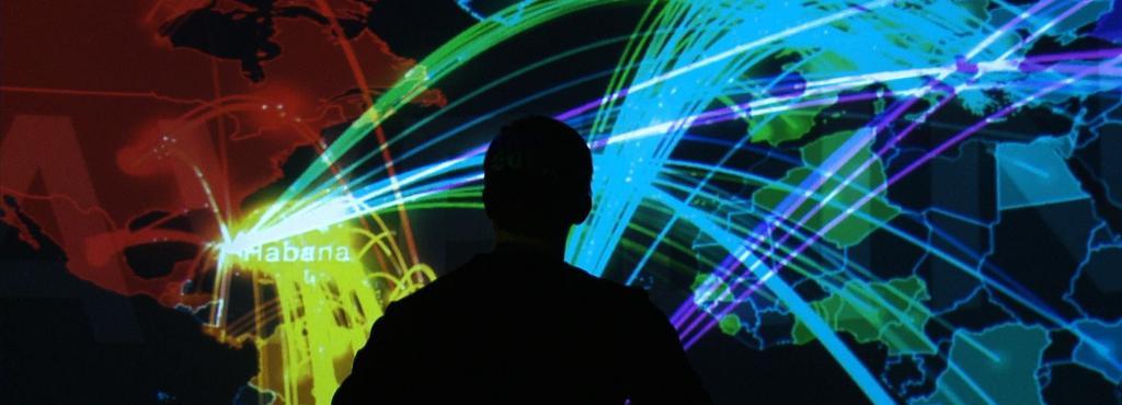 Schatten einer Person steht vor einem Panoramascreen auf dem trans_actions gezeigt wird