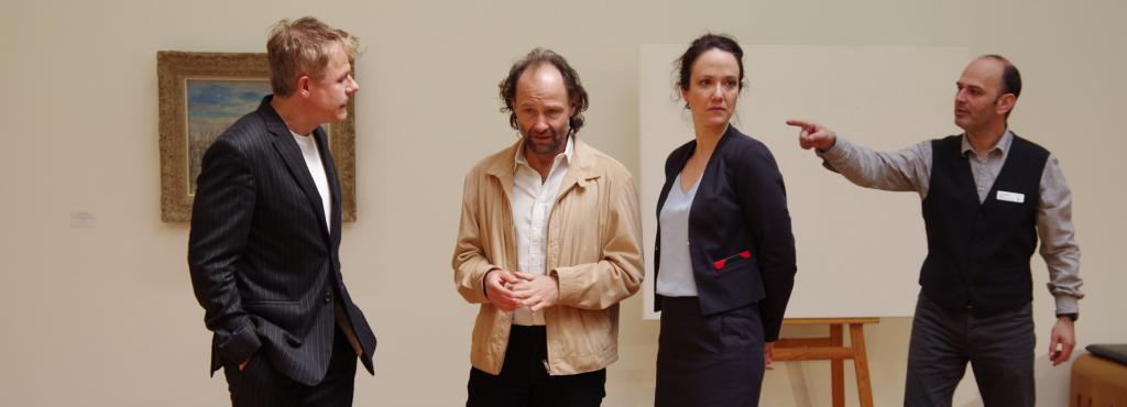 Vier Menschen stehen nebeneinander auf einer Bühne.