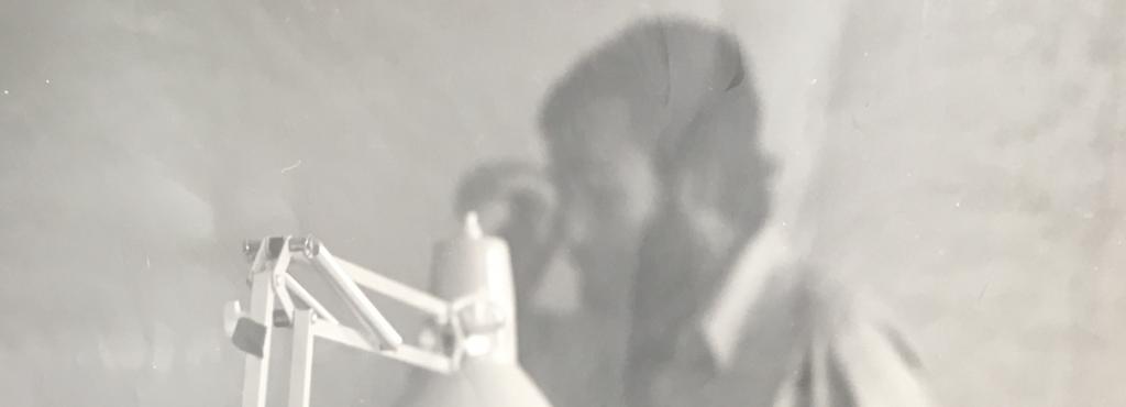 Eine Schwarz Weiß Fotographie zeigt im Vordergrund scharf eine Schreibtischlampe. Im Hintergrund sind man unscharf einen Mann mit Bart und einem weißen Hemd.