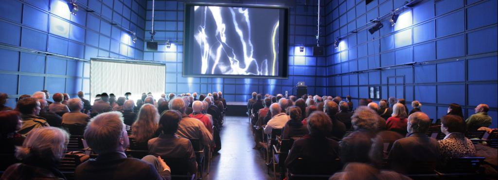 The ZKM_Media Theater full of people who look at a canvas which shows amorphous structures in white