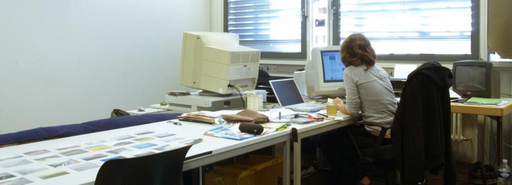 A person working at the computer, photographed from behind