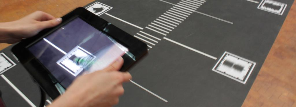 Cut a path full of QR codes. A hand that scans the QR codes with an iPad