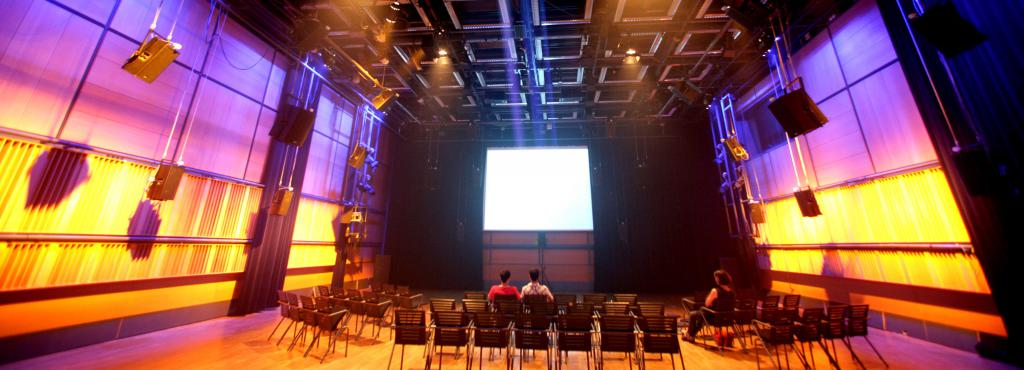 A white screen in the background. Previously, a number of chairs. The side walls are bathed in a purple and yellow light.