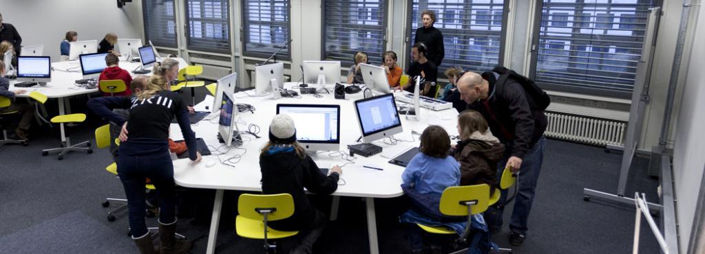 Mehrere Personen sitzen an einem rundem Tisch an Computern