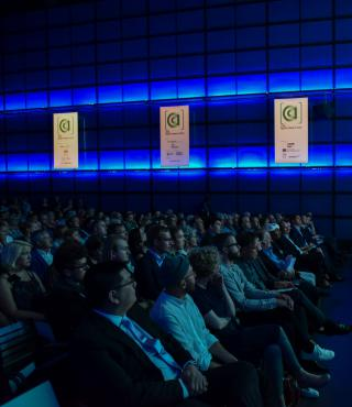 The audience of the AppArtAward award ceremony 2016 is sitting in the ZKM_Media Theater which is illuminated in blue light.