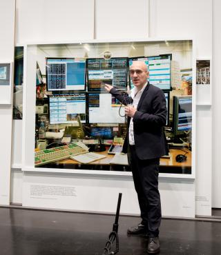 A man stands in front of a picture and talks about it