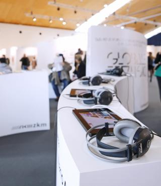 A curved counter, on which iPads and headphones are lying