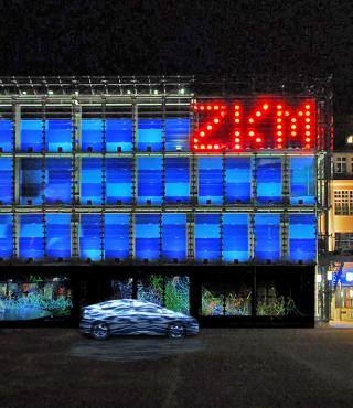 A car stands in front of the blue cube. Top right in big red glowing letters: ZKM