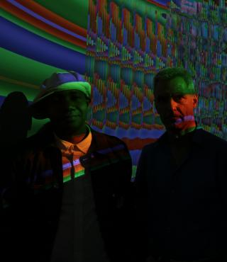 Two men standing in a dark room in front of a screen with colorful colors.