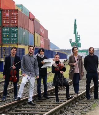 The IEMA-Ensemble infront of a harbor scenery with containers and a crane