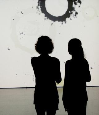 Zwei Besucherinnen vor einer Tambellini Video-Leinwand
