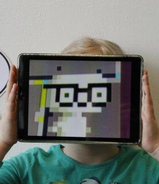 """Performance of a girl, that is holding an iPad in front of her face. The display shows a creature buid of pixels. Next to her, the word """"sweet"""" is written in a speech bubble."""