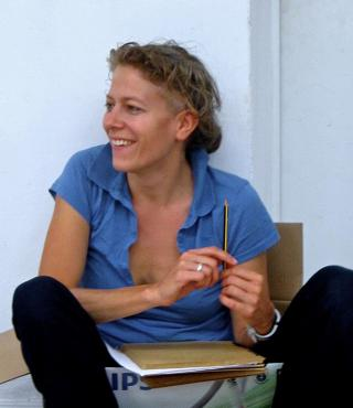 Anja Konjetzky sits casually in a cardboard box and holds a pencil in her hand.