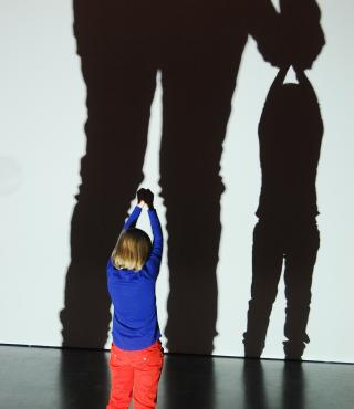 A child is standing in front of a screen, shaddows of two persons are cast on the wall. It looks as though the child is beeing held up by a giant.