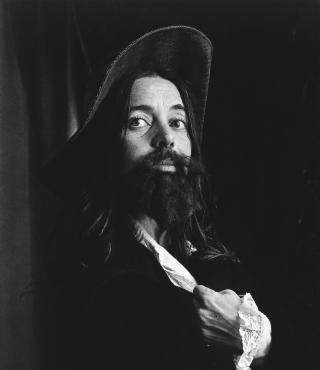 Das Schwarz-Weiß-Foto zeigt eine Frau, die einen Hut und einen Bart trägt