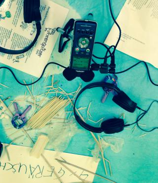 A Fieldrecorder, headphones, wooden sticks, papers and a plier are on turquoise background.