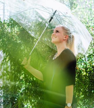 Frau steht mit Regenschirm unter der Raindance-Installation