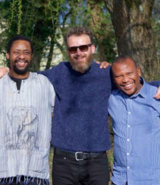Das Bild zeigt die vier strahlenden Mitglieder von Bänz Oester & The Rainmakers